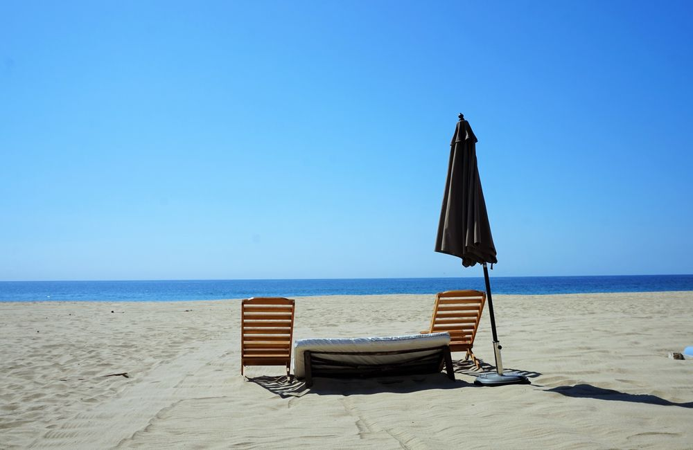 beach setting with two chairs and umbrella